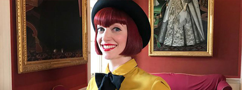 Amber Butchart wears a mustard yellow blouse with a jaunty black bow and hat