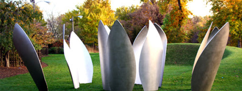 Silver lotus petal sculpture sits in a green lawn.
