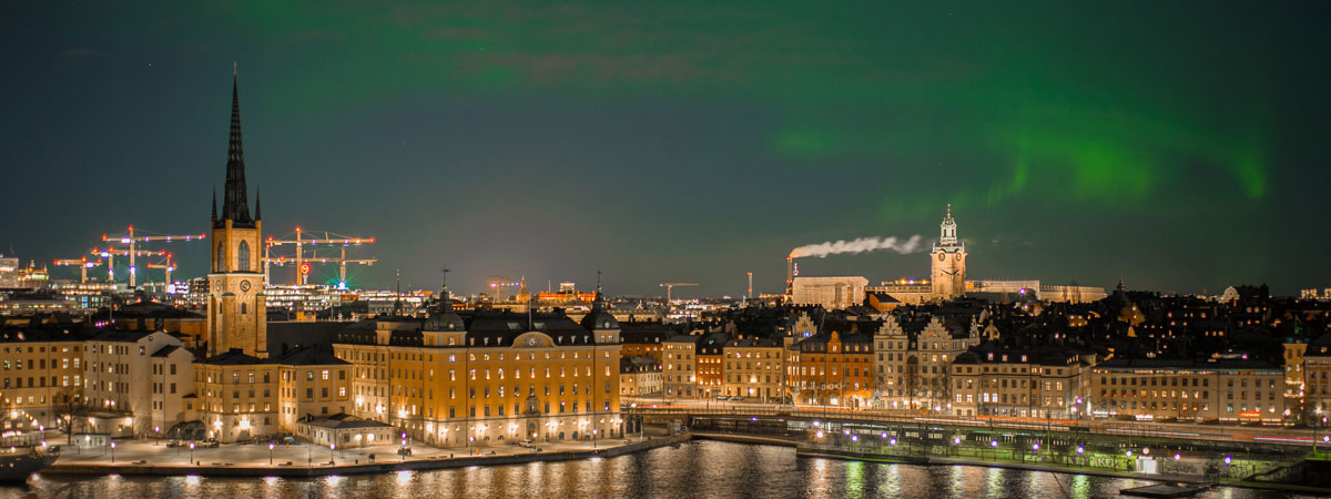 The golden skyline of Stockholm against a dark sky with green flashes of the Northern Lights.