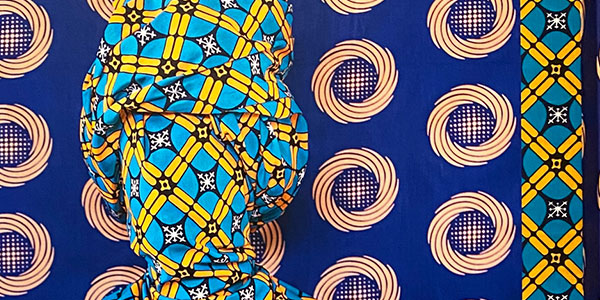A small portion of a photography image from artist Alia Ali. A human head is wrapped in a bright blue and yellow fabric and pops out from a blue and white fabric background.