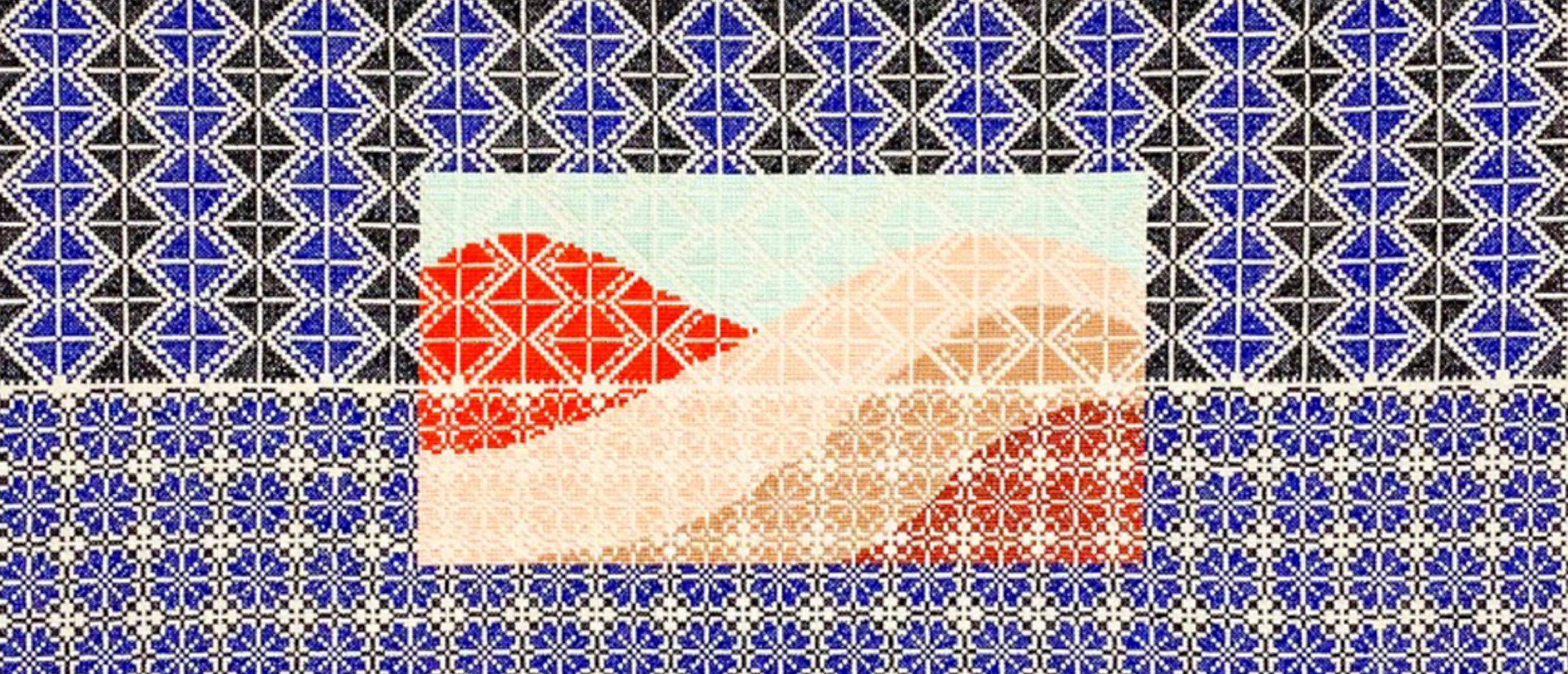 A cross stitch design in blue, black and white with an depiction of the Palestinian desert in shades of orange and taupe. A pattern designed by Jordan Nassar.
