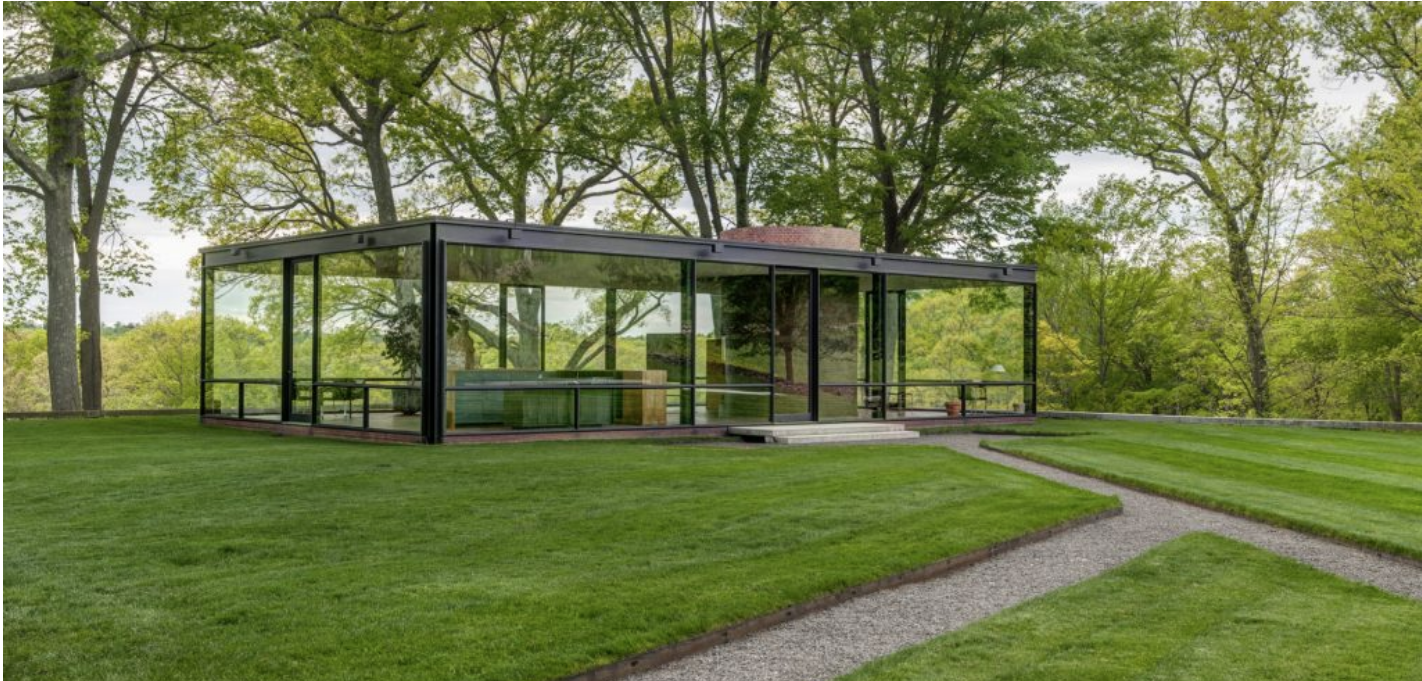 A mid-century modern glass house sits in a forested lawn.